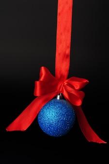 Weihnachtsflitter, der am roten satinband gegen schwarzen hintergrund hängt