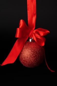 Weihnachtsflitter, der am roten satinband gegen schwarzes hängt