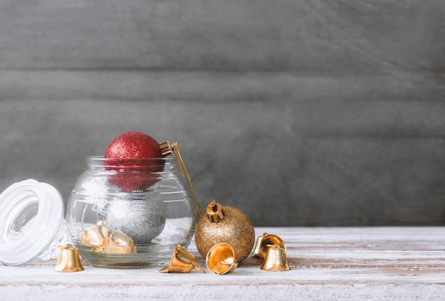 Weihnachtsflitter und glocke auf weißem hölzernem tabellenhintergrund