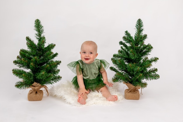 Weihnachtsfoto ein kleines kindermädchen, das nahe den weihnachtsbäumen in einem grünen kleid auf weiß sitzt