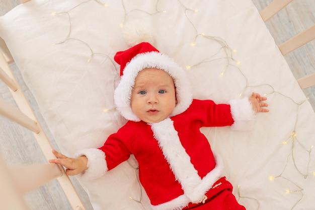 Weihnachtsfoto eines babys in einem weihnachtsmannanzug, der in einem kinderbett zu hause liegt, draufsicht, frohes neues jahr.