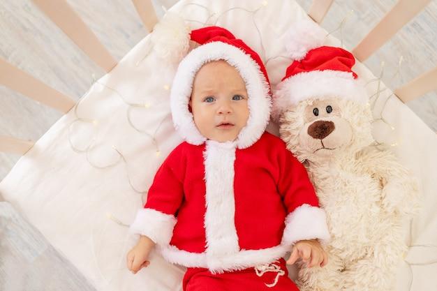 Weihnachtsfoto eines babys in einem weihnachtsmannkostüm, das in einem kinderbett zu hause mit einem spielzeug in einer weihnachtsmannmütze liegt