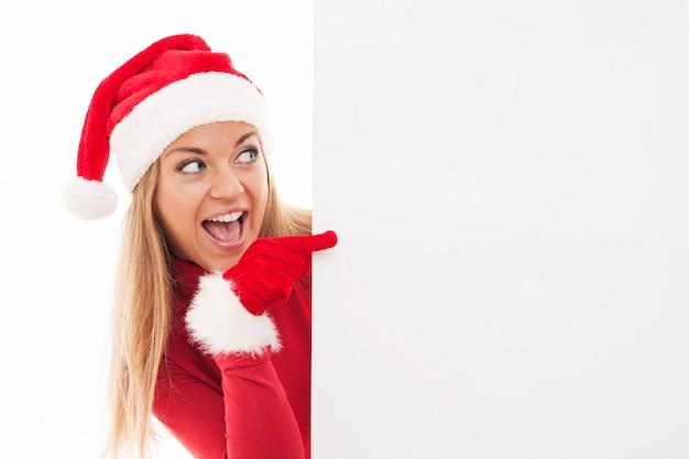 Weihnachtsfrau, die auf copyspace zeigt