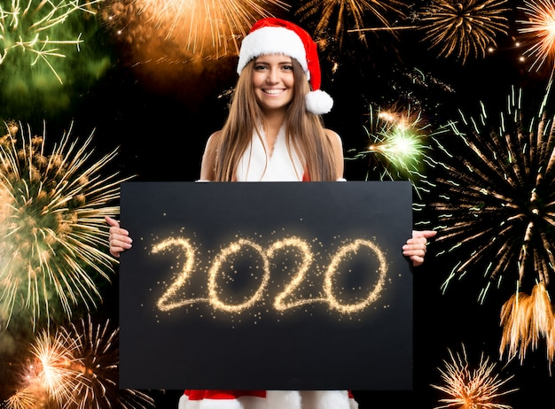 Weihnachtsfrau, die eine glückliche karte mit 2020 wünschen hält