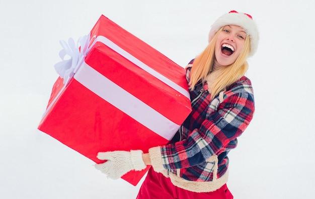Weihnachtsfrau, die eine riesige geschenkbox hält. frohe winterzeit. hipster girl mit weihnachtsgeschenk auf schnee winterlandschaft. weihnachten winter menschen.