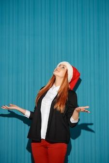 Weihnachtsfrau, die eine weihnachtsmütze trägt und aufschaut