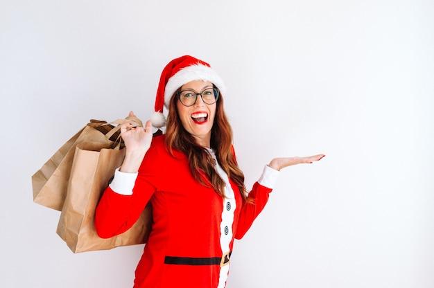 Weihnachtsfrau frohes vorbildliches mädchen in sankt-hutzeigende hand
