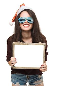 Weihnachtsfrau halten große weiße karte. weihnachtsmütze. isoliertes lächelndes mädchen. weihnachtsbaum