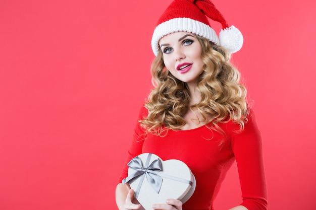 Weihnachtsfrau in der weihnachtsmütze, die geschenk hält. neujahrs- oder weihnachtskonzept
