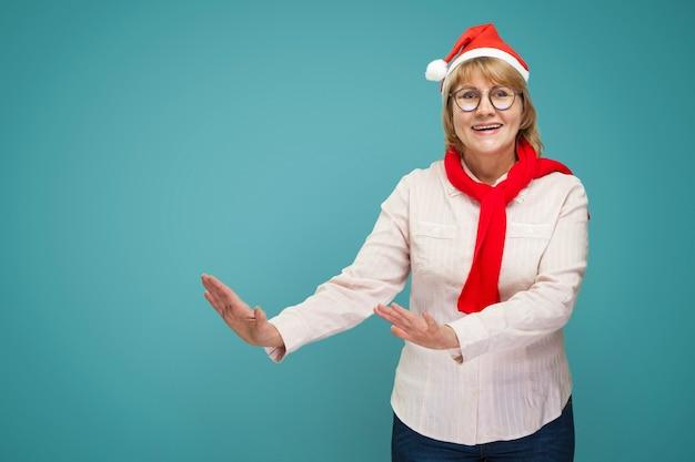 Weihnachtsfrau in weißem hemd und jeans auf blauem hintergrund