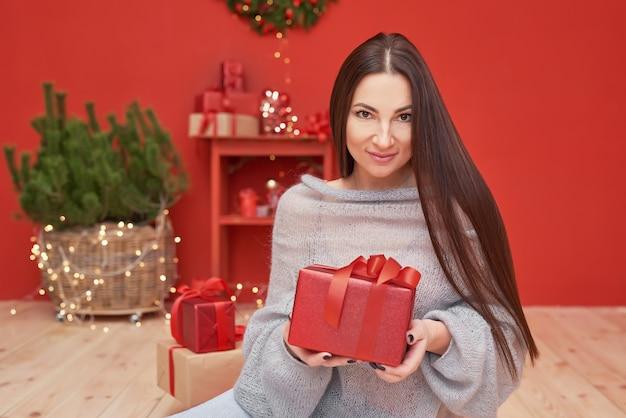 Weihnachtsfrau mit geschenken nahe weihnachtsbaum