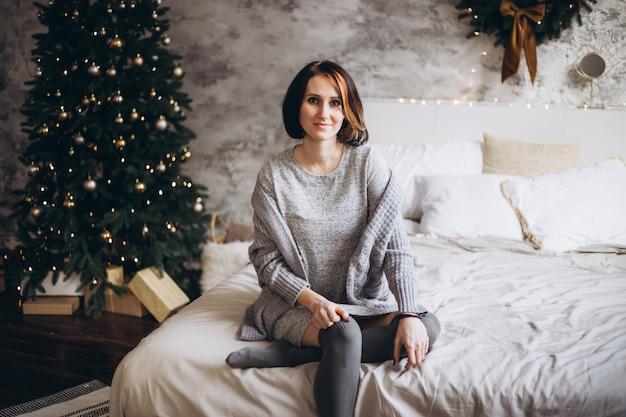 Weihnachtsfrau nahe einem weihnachtsbaum auf bett zu hause