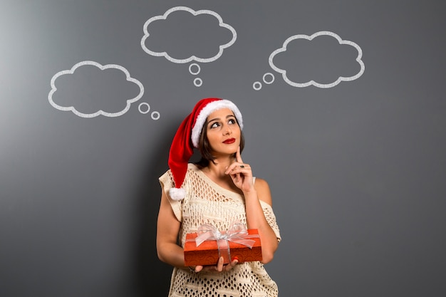 Weihnachtsfrau suchen nach oben leere kopie raum halten geschenkbox geschenk, junge glückliche lächeln frau tragen weihnachtsmann hut, attraktive neujahr party mädchen, über tafel mit leeren ballons