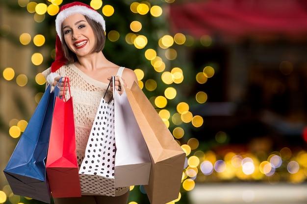Weihnachtsfrauenporträt, das einkaufstaschen hält. lächelnde glückliche frau über bokeh-weihnachtslichtern