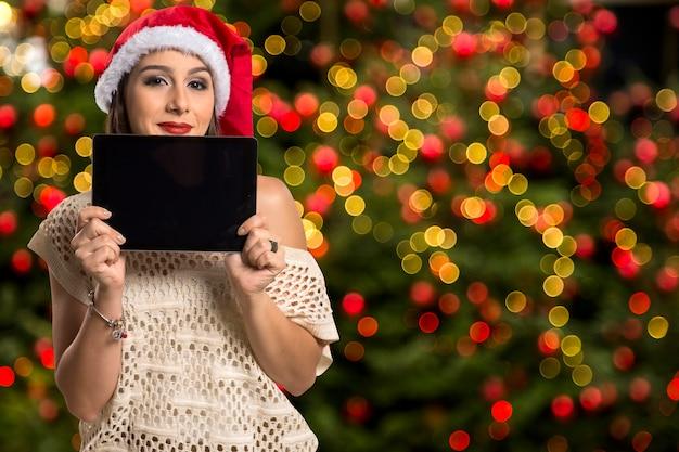 Weihnachtsfrauenporträt, das tablette hält. lächelnde glückliche frau über weihnachten bokeh lichter