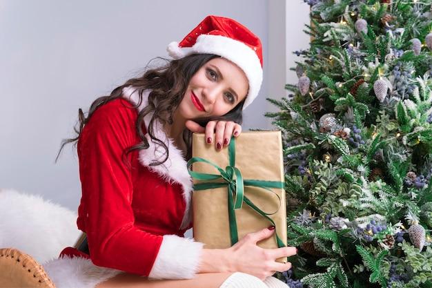 Weihnachtsfrauenporträtgriff weihnachtsgeschenk. lächelndes glückliches mädchen auf weihnachtsbaumhintergrund. junge frau öffnet ein weihnachtsgeschenk.