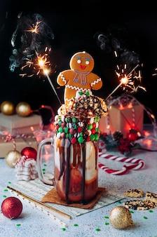 Weihnachtsfreak-shake mit wunderkerzen-bengal-lichtern, die mit lebkuchenmann auf partytisch übersteigen