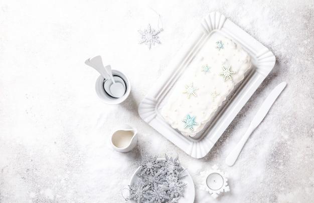 Weihnachtsfrucht-kuchen, pudding auf schneebedecktem hintergrund. neujahrsgebäck