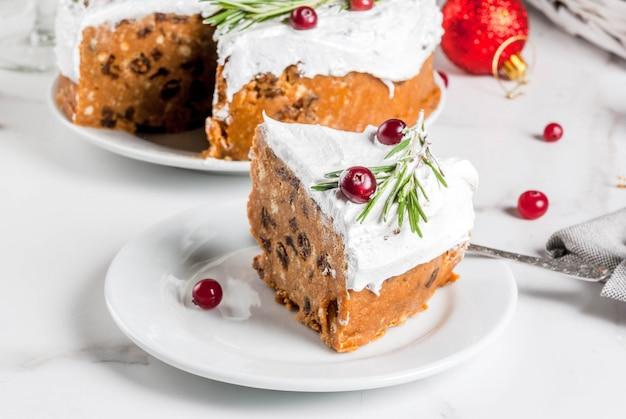 Weihnachtsfruchtkuchen oder -pudding, verziert mit rosmarin und moosbeere, mit weihnachtsdekoration, auf weißer marmortabelle, kopienraum