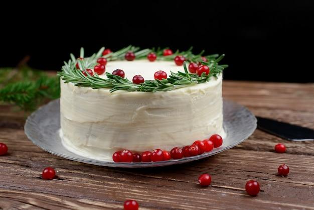 Weihnachtsfruchtkuchen, pudding auf teller mit rosmarin und cranberry-dekor