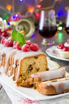 Weihnachtsfruchtkuchen und weihnachtsdekoration auf einem rustikalen holztisch