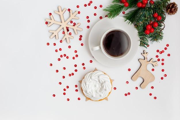 Weihnachtsfrühstück mit einer tasse kaffee und einer weißen baisertorte auf einem weißen tisch mit neujahrsdekor: holzspielzeug, eine schneeflocke, ein reh, ein fichtenzweig. speicherplatz kopieren. draufsicht
