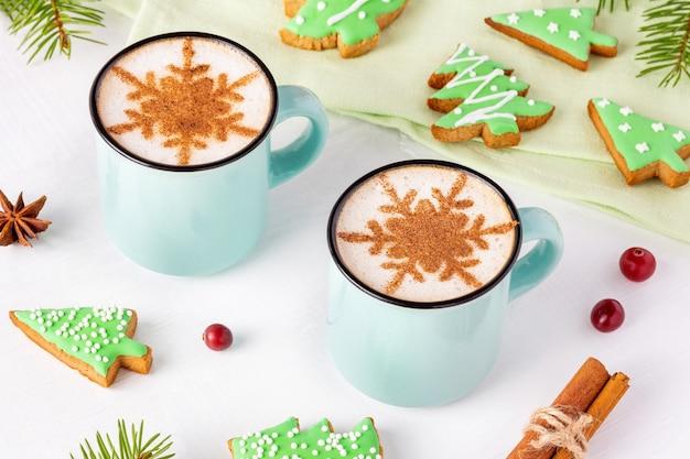 Weihnachtsfrühstück mit tannenbaumförmigen keksen und latte mit zimtschneeflocken auf weißem hintergrund.