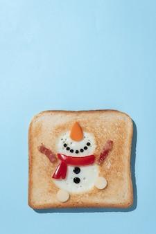 Weihnachtsfrühstück: toast mit eiweiß in form eines fröhlichen schneemanns