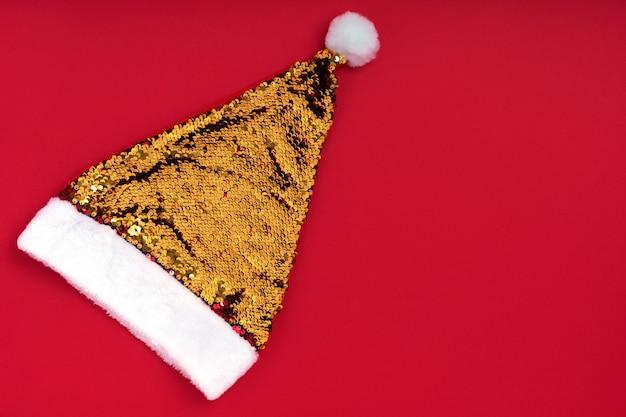 Weihnachtsfunkelnder goldener weihnachtsmann-hut auf rot. feiertagshintergrund des weihnachtsweihnachtsneuen jahres. neujahr zubehör. frohe weihnachten grußkarte. draufsicht, flache lage, copyspace