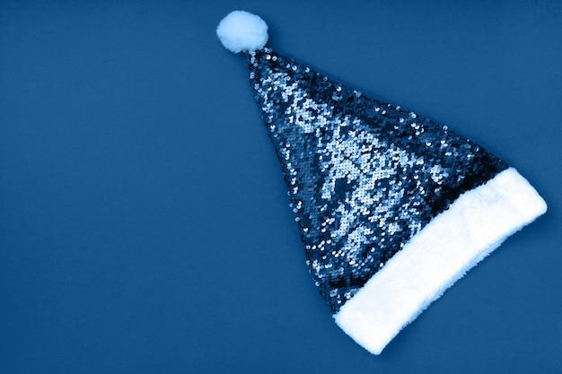 Weihnachtsfunkelnder weihnachtsmann-hut auf blauer oberfläche