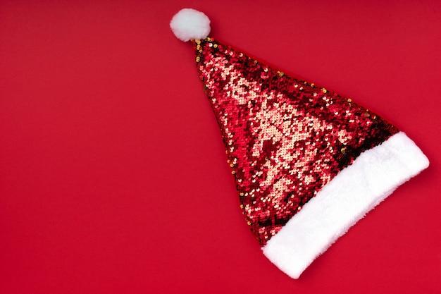 Weihnachtsfunkelnder weihnachtsmann-hut auf rotem hintergrund. feiertagshintergrund des weihnachtsweihnachtsneuen jahres. neujahr zubehör. frohe weihnachten grußkarte. draufsicht, flache lage, kopienraum