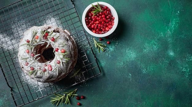 Weihnachtsgebackener dunkler schokoladenbündelkuchen, der mit puderzucker und frischen preiselbeeren auf metalldrahtgestell dunkelgrünem hintergrund verziert wird