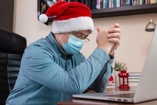Weihnachtsgebet online. älterer mann im weihnachtsmannhutgebet unter verwendung des laptops für videoanruffreunde und -kinder. das zimmer ist festlich eingerichtet. weihnachten während des coronavirus.