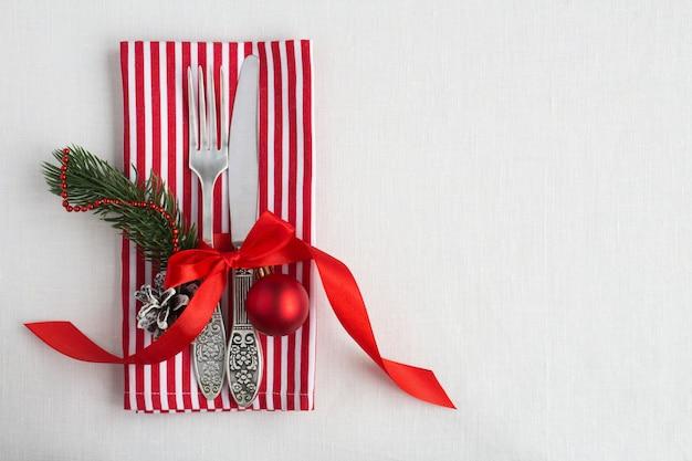 Weihnachtsgedeck auf der gestreiften serviette auf der weißen textiloberfläche. draufsicht. speicherplatz kopieren.