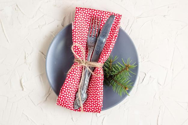 Weihnachtsgedeck mit gabelmesserservietten- und -tannenbaumbrunch auf weißer tabelle. textfreiraum, ansicht von oben