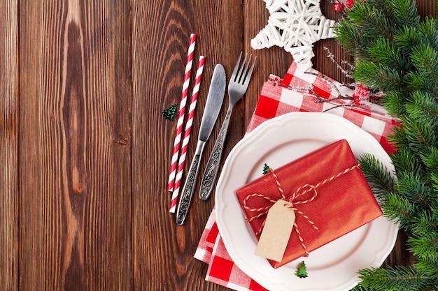 Weihnachtsgedeck mit geschenkbox und tannenbaum auf holztisch. draufsicht mit kopienraum