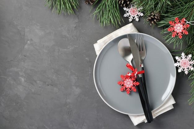 Weihnachtsgedeck mit grauer platte und hölzernen schneeflocken auf grauem tisch. ansicht von oben. zu hause bleiben. platz für text