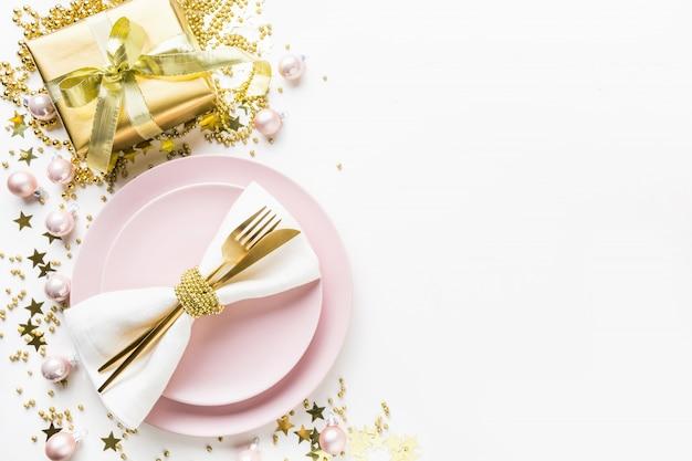 Weihnachtsgedeck mit rosa dishware, goldenes tafelsilber auf weiß. ansicht von oben.