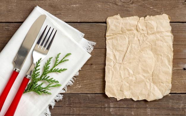 Weihnachtsgedeck - weiße serviette, gabel und messer draufsicht mit papier auf einem holztisch