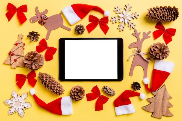 Weihnachtsgelb mit feiertagsspielwaren und -dekorationen.