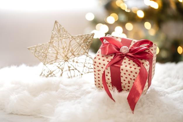Weihnachtsgeschenk auf dekorativem sternhintergrund auf unscharfem bokeh hintergrund schließen oben.