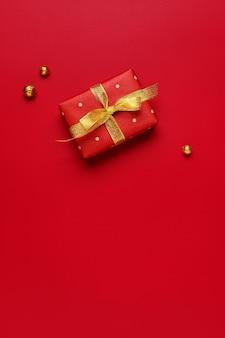 Weihnachtsgeschenk auf rotem feiertagshintergrund mit kopienraum.
