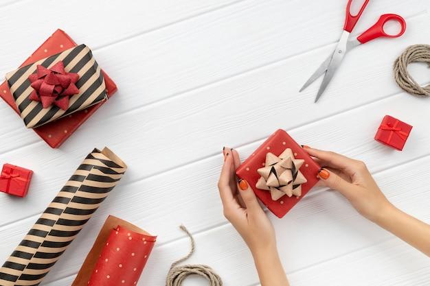Weihnachtsgeschenk, das über weißen holztisch wickelt. draufsicht, flache lage, kopierraum