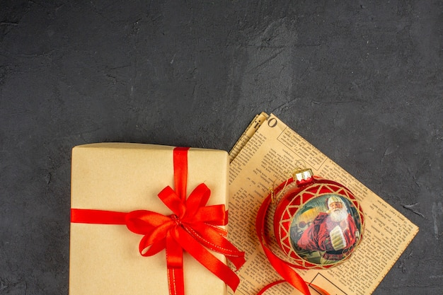 Weihnachtsgeschenk der oberen hälfte in braunem papierband-weihnachtsbaumspielzeug auf zeitung auf dunklem hintergrund