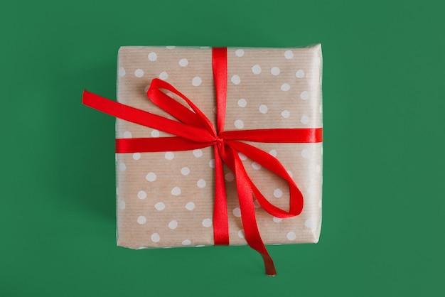 Weihnachtsgeschenk eingewickelt in kraft tupfenpapier mit rotem band auf grünem hintergrund