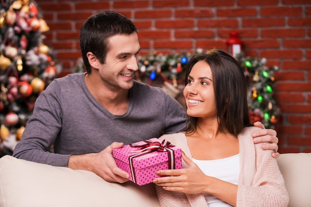 Weihnachtsgeschenk für sie. hübscher junger mann, der seiner freundin eine rote geschenkbox gibt und mit weihnachtsbaum im hintergrund lächelt