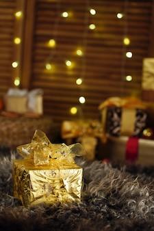 Weihnachtsgeschenk, geschenkbox in goldfolie verpackt und mit einem band gebunden