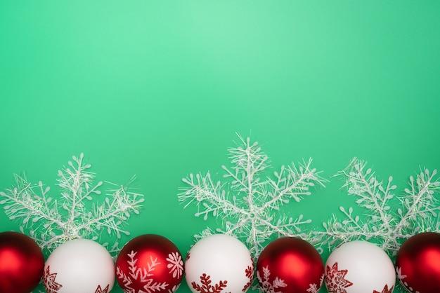 Weihnachtsgeschenk, -glocke und -ball auf grünem hintergrund. flache lage, draufsicht