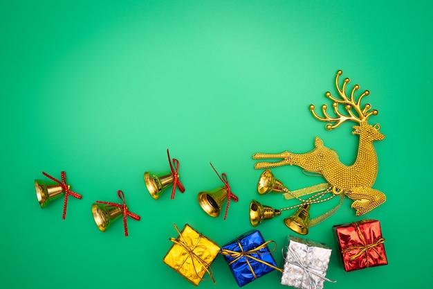 Weihnachtsgeschenk, goldren und glocke auf grünem hintergrund. flache lage, draufsicht