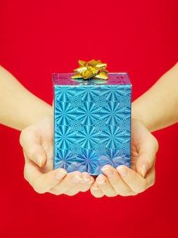 Weihnachtsgeschenk in den händen lokalisiert auf rot